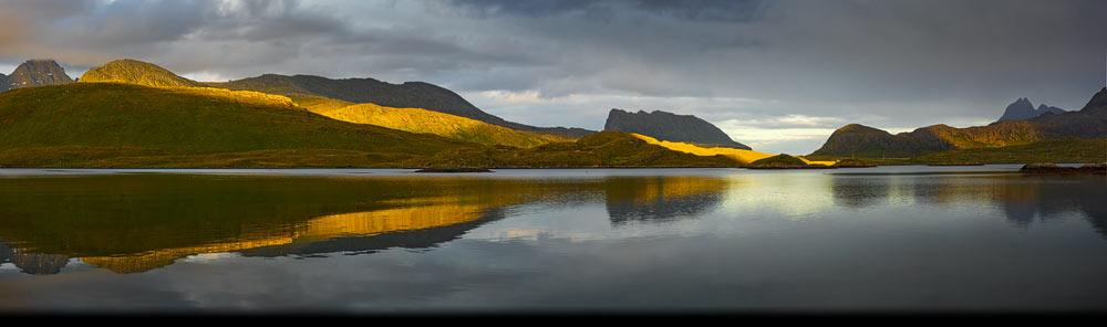 Middernachtzon over de bergen van Flakstadoya op de Lofoten in het noorden van Scandinavië
