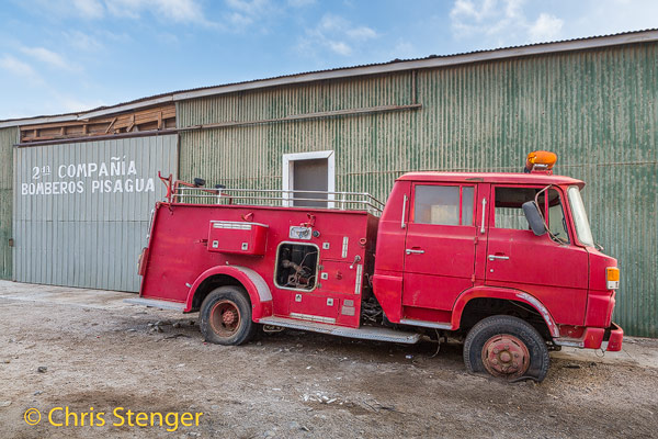 Ook dit wrak van een brandwerauto bij de brandweerkazerne van de oude havenplaats Pisagua in het noorden van Chili ademt de sfeer van vergane glorie