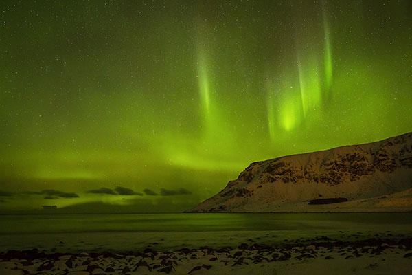 Noorderlicht (Aurora borealis) boven de kust bij het plaatsje Unnstad op de Lofoten