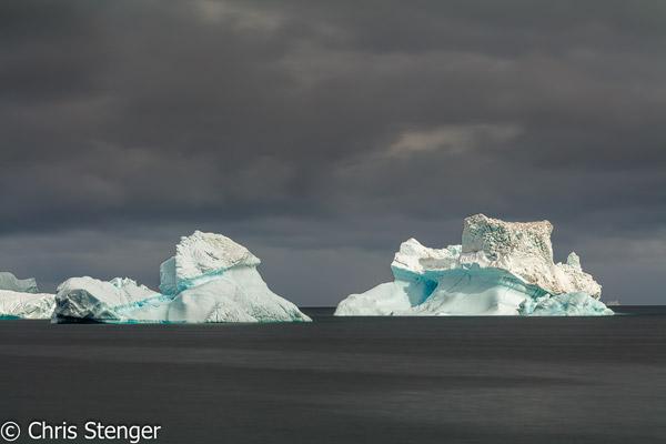 Witte IJsbergen steken af tegen een dreigende lucht in de Disko baai in west Groenland