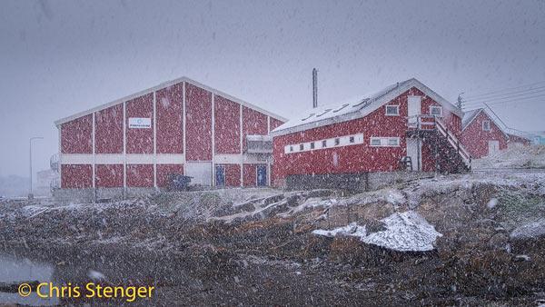 De rode huisjes in Qeqertarsuaq op Disko eiland in Groenland verdwijnen in een flinke sneeuwbui