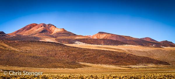 Panorama opname van een vulkaan met gestolde lavastromen aan de rand van de Salar de Huasco