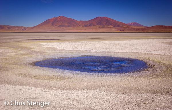 De zoutvlakte Salar de Huasco met een klein zoutmeertje op de voorgrond en vulkanen op de achtergrond