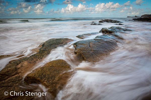 De rotspartijen op het strand zijn het meest interessant als de vloed opkomt. Het water vormt dan onderdeel in de foto. De belichtingstijd van 1 sec werd bereikt door een 64x ND filter te gerbuiken