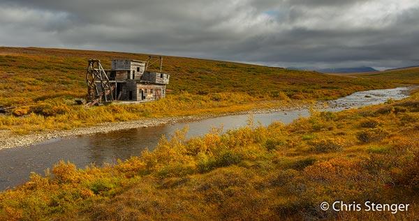 Op veel plaatsen in de omgeving van Nome vind je overblijfselen uit het goldrush tijdperk, waaronder deze golddredge op de herfstige toendra