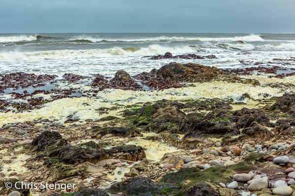 Rolsten en wat lage rotsen; dat is de Namibische kust in het noorden. Het licht gele spul in het midden van de foto is schuim dat ontstaat in de branding