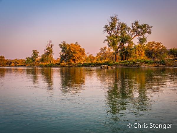 De Kunene rivier is een soort oase in het droge Namibië. Langs de rivier groeien bossen, een paar kilometer van de rivier slaat de droogte weer toe