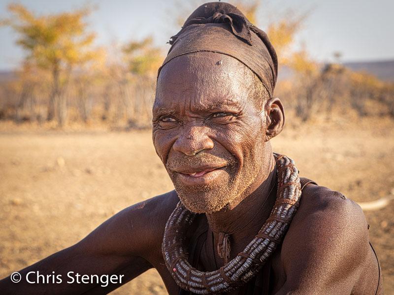 Ik maakte dit protret in het vroege ochtendlicht voor de hut van zijn familie. Hij draagt de traditionele halsketting die vrijwel iedere Himba draagt in het dagelijkse leven.